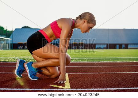 Young woman athlete at starting position ready to start a race. Female sprinter ready for sports exercise on racetrack.