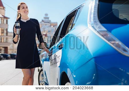 Home made tea. Pleasant smart delighted businesswoman smiling and opening a door of her car while having a thermo cup with tea in her hands