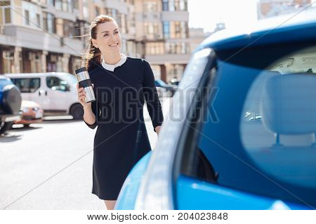 Warm drink. Cheerful positive nice businesswoman standing near her car and drinking tea while holding a thermo cup
