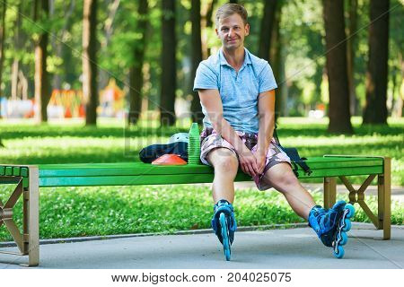 Portrait of happy handsome male roller in inline roller skates sitting on bench on the park.