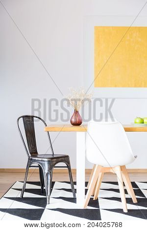 black and white chair at dining table with red vase in contrast color room with geometric carpet and gold painting