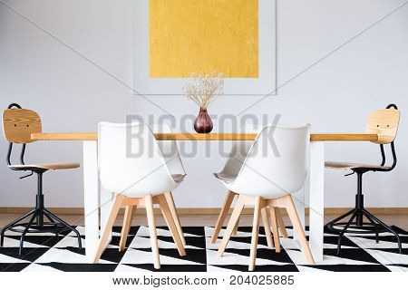 Symmetric set of white chairs at dining table with decorative vase in dining room with gold painting