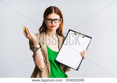 A strict teacher with a mosk up a4 sheet indignantly shows her hand up, displeased face. Young female student is angry
