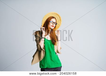 Young stylish woman in a green jacket and jacket holds a straw hat