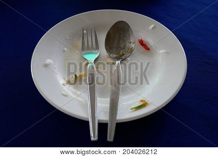 White plate with food scraps,Dirty white plate and spoon.