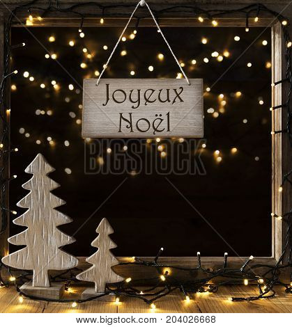 Sign With French Text Joyeux Noel. Window Frame With Lights In The Night In Background. Christmas Decoration Like Christmas Tree And Fairy Lights.