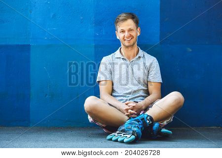 Happy Handsome Young Roller In Inline Skates Sitting Against Blue Wall.