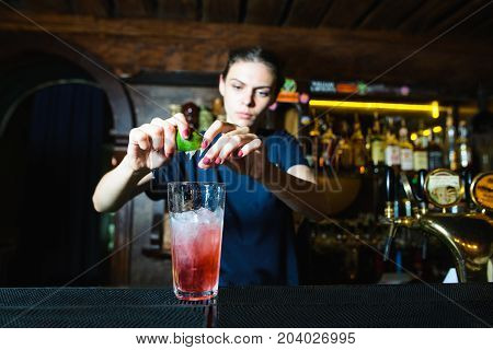 The bartender girl creates a nice cool red cocktail at the bar. The barman squeezes lime juice into an alcoholic cocktail