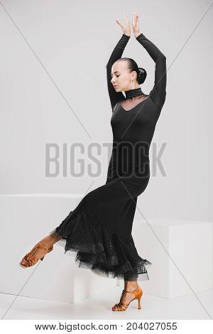 pretty girl in black dress dancing in studio, dancer posing and looking down