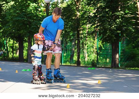 Portait of cute baby boy with inline skating instructor in the park learining to skate.