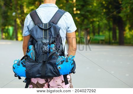 Young male roller skater standing with roller backpack. Shoot from behind.