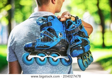 Young Male Roller Skater Holding Inline Roller Skates.