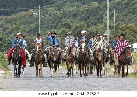 May 27 2017 Sangolqui Ecuador: a group of cowboys riding their horses on a country road towards a rural rodeo in the Andes