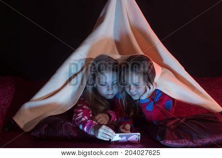Girls With Interested Faces Lie Under Blanket On Black Background