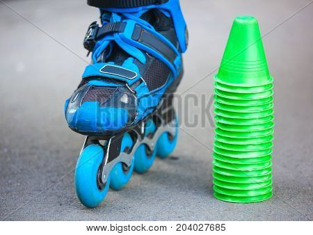 Blue Roller Skates With Slalom Cones Lying On Asphalt.