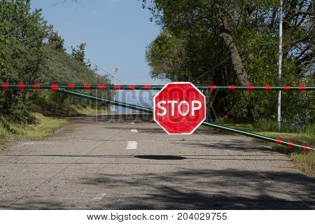 Road sign attached to the barrier. Photo in the daytime.