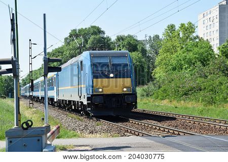 Passenger train is coming at the road crossing