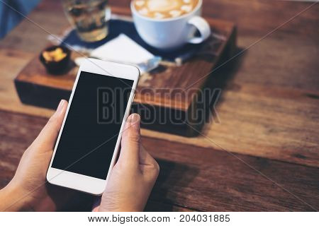 Mockup image of a woman's hands holding white mobile phone with blank black screen with coffee cup tea and snack on wooden table in vintage cafe