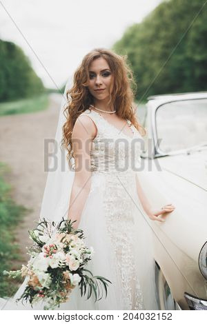 A beautiful bride posing near retro car outdoors.