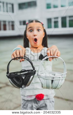 pretty teen holding white and black headphones, cute girl dressed in a white blouse with a black bow chooses headphones