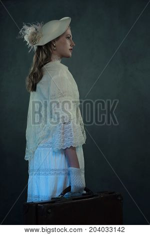 Victorian Girl In White Dress And Hat Holding Suitcase.