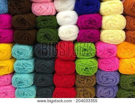 Pile of colorful knitting yarn on shelf in store