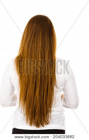 Woman standing backwards showing her long brown healthy hair. Haircare and hairstyling concept.