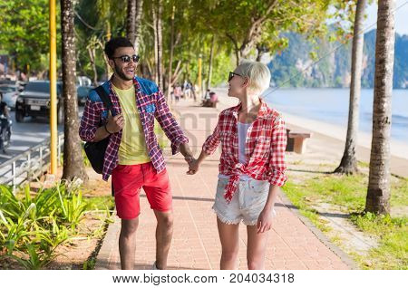 Casual Couple Hold Hands Walking In Tropical Palm Trees Park, Beautiful Young People On Summer Vacation, Latin Man And Blonde Woman Holiday Travel