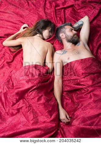 Couple In Love On Burgundy Sheets. Man And Woman