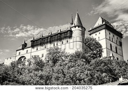 Large gothic castle Karlstejn in Czech republic. Ancient architecture. Travel destination. Black and white photo.