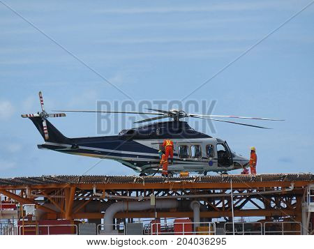 Helicopter or chopper land at oil and gas platform area for get and sent passenger from onshore hangar to offshore platform. Ground staff fill the gas tank( jet-A1 fuels) in helicopter.