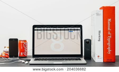 PARIS FRANCE - SEP 13 2017: Minimalist creative room table with Safari Browser open on MacBook Pro Pro laptop showcasing Apple Computers website with latest iPhone 8 and 8 Plus with glass body
