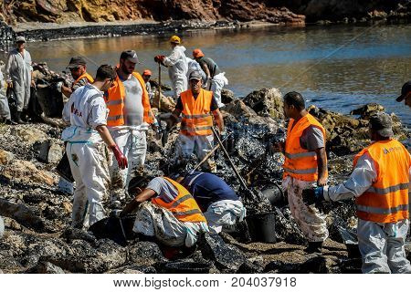 Workers Try To Clean Up Oil That Has Washed Ashore, On A Beach Of Salamis Island Near Athens, After