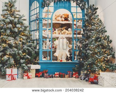 Christmas magical atmosphere background. Modern interior design for winter holidays. Pine trees decorated with shining lights, showcase with toys and present boxes