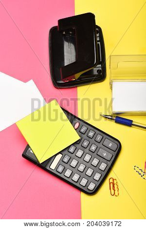 Office Stationery And Calculator On Yellow And Pink Background