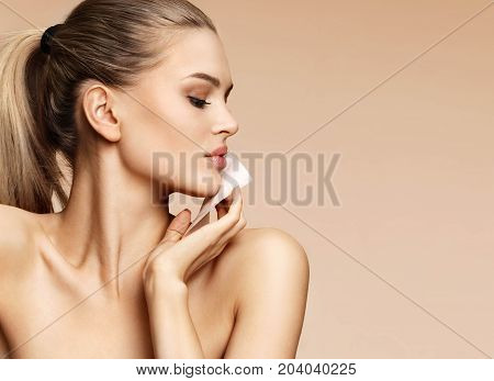 Skin care. Young girl in profile removing oil from face using blotting papers. Photo of beautiful blonde girl on beige background. Beauty concept