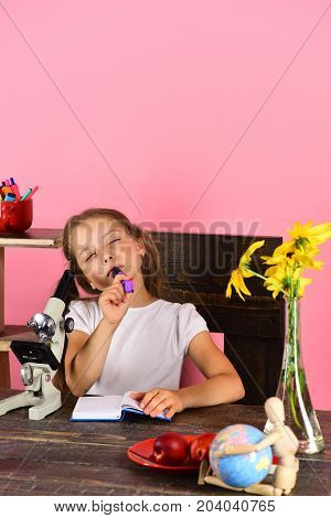 Schoolgirl At Desk With Yellow Flowers, Microscope And Globe