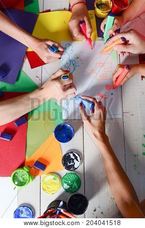 Artists Wooden Table With Paints And Colored Paper