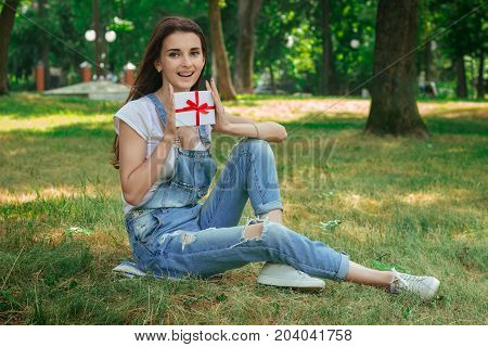 fun charming brunette sits on the grass and holding a gift