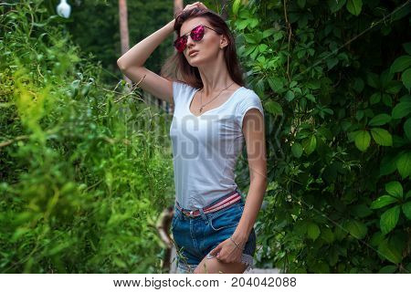 attractive slender women in mirrored sunglasses posing amid greenery