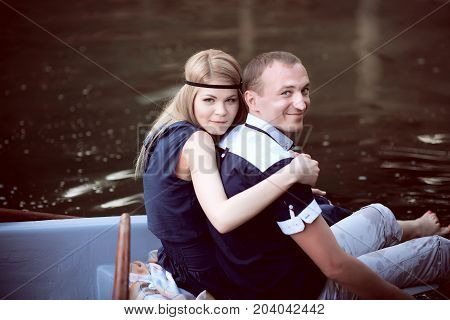 sweet man and woman sitting on the edge of boat, beautiful teenager having fun in a boat outdoors, happy couple have fun in a boat on the lake