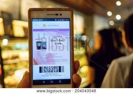 Bangkok Thailand - Sep 8 2017: Hand holding smart phone opening Starbucks Buy 1 Get 1 Free campaign Online coupon against blur Starbucks customers waiting in line at coffeehouse to buy coffee.