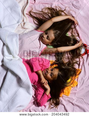 Schoolgirls In Pink Pajamas Wallow On Colorful Pillows, Top View.