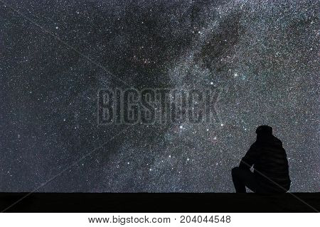 Milky Way. Night sky with stars and silhouette alone man looking at starry sky.