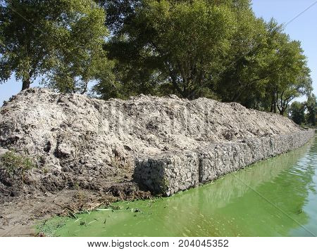 The riverbank is fortified with gabions .