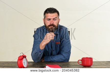 Man With Puzzled Face Sits At Wooden Table