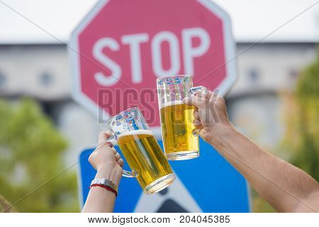 Close up of two hands holding mugs of beer in front of stop street sign. Alcohol abuse and alcoholism prevention. Don't drink and drive concept