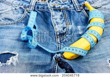 Banana wrapped with blue measure tape on jeans selective focus. Mens denim pants crotch with banana imitating male genitals. Jeans zipper and pocket close up. Health and male sexuality concept.