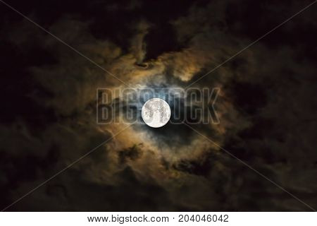 Full moon amongst thunderclouds in the night sky