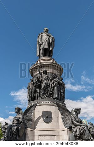 Dublin Ireland - August 7 2017: Tall and big black Daniel O'Connell Statue on light gray pedestal against blue sky shows the person with angels women and men statues.
